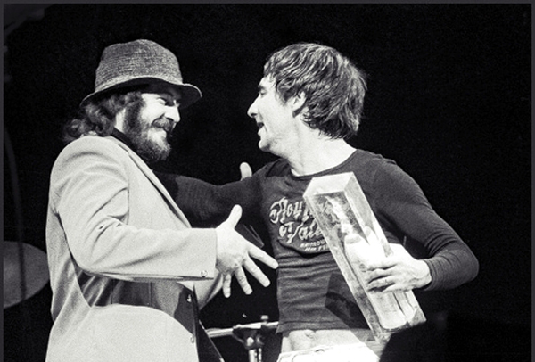 Drummers John Bonham (1948-1980) from Led Zeppelin and Keith Moon (1946-1978) from The Who present spoof awards on stage during a concert featuring Roy Harper and Friends at the Rainbow Theatre in Finsbury Park, London on 14th February 1974. (Photo by Dick Barnatt/Redferns)